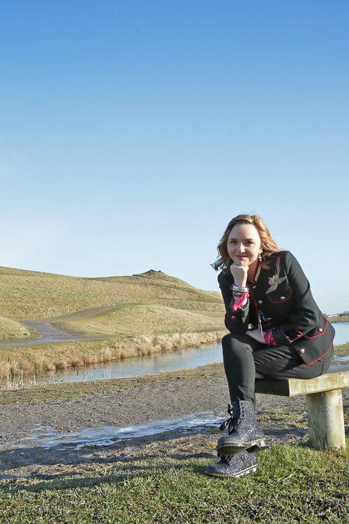 Photo of Ceryn Rowntree sitting an a bench outdoors facing the camera with her chin propped up on her hand. Behind her are blue skies and a green hill. Photo by Laura Pearman.