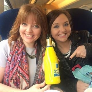 A photograph of two women on a train, holding up an open yellow champagne bottle
