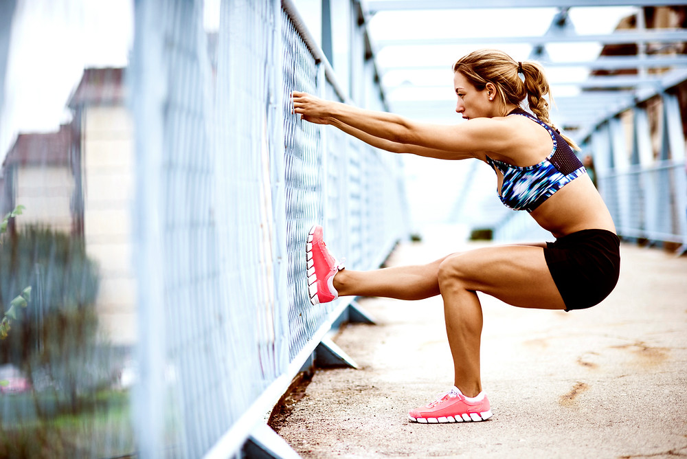 Woman using fence to stretch her body outside before running