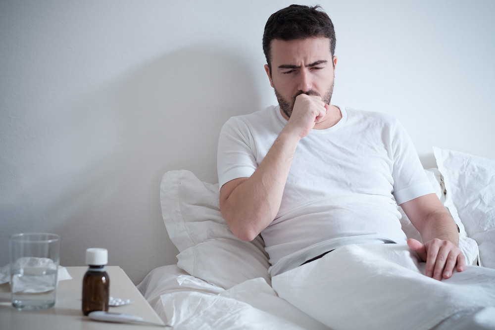 Man sick in bed with a cold or flu.