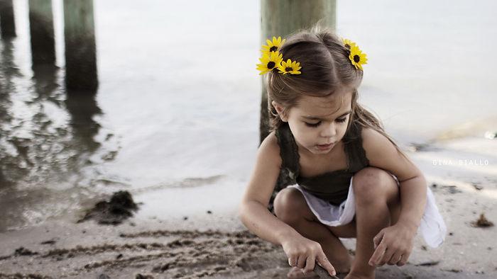 ребенок рисует на песке