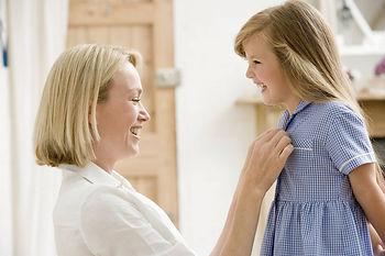 мама застегивает дочке платье