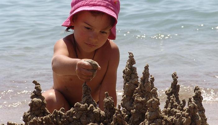 замок из песка, девочка строит замок на пляже