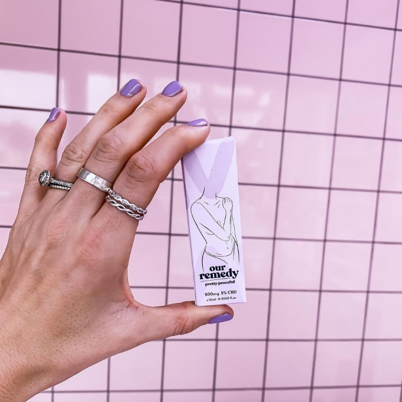 A white box of Our Remedy being held up in front of a pink wall