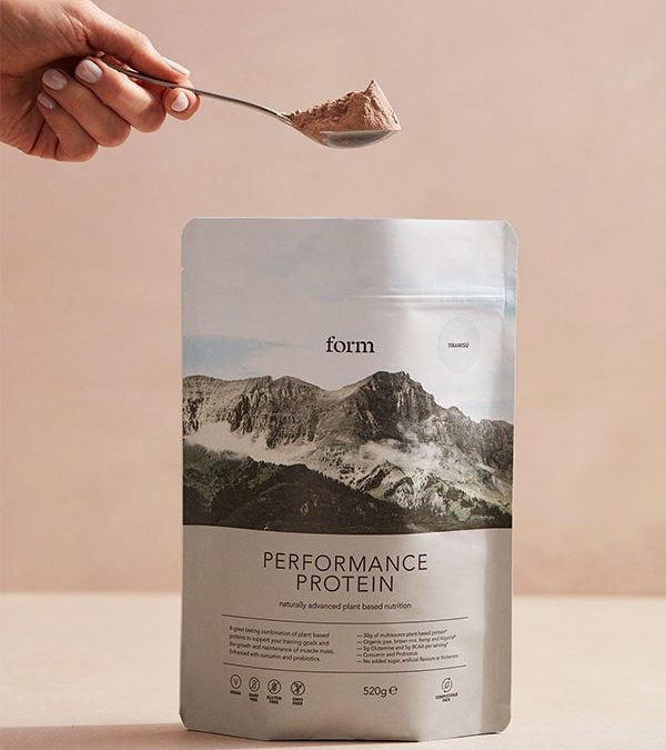 Form Nutrition Performance Protein packed with a hand holding a scoop of the powder.