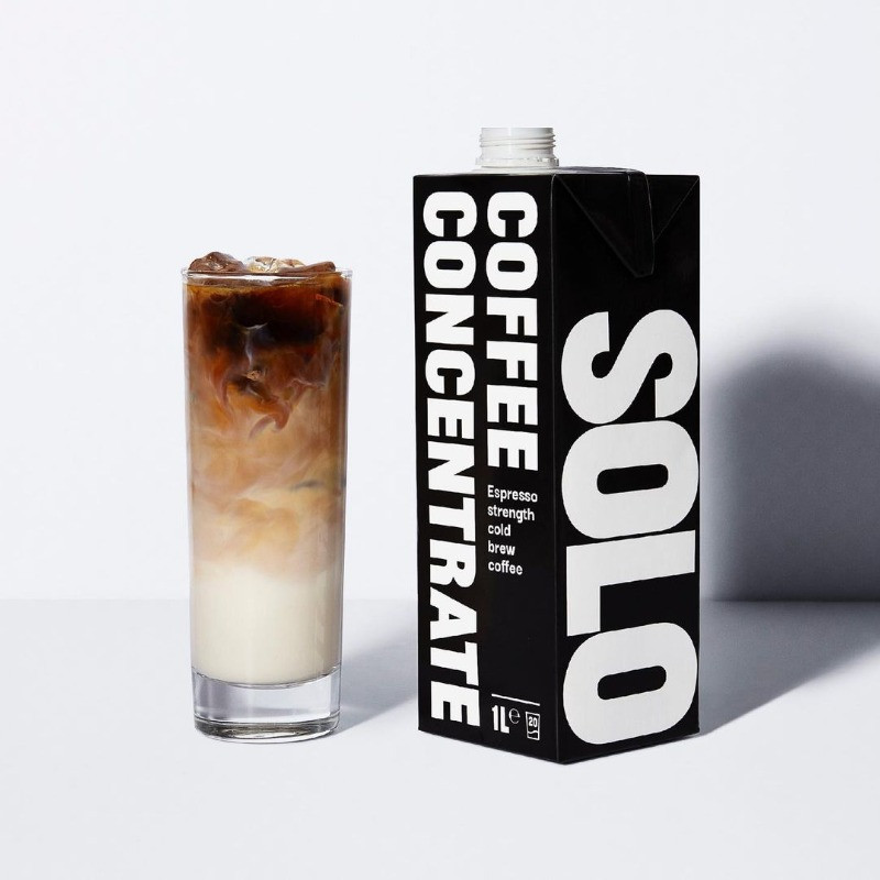 a black box with the words solo coffee on next to an iced latte in a tall glass