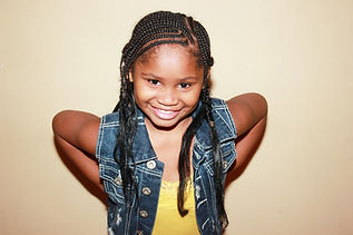 happy smiling young black girl with corn row braids