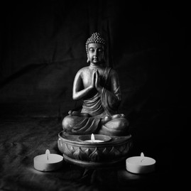 Meditating Buddah statue with candles  (B & W), 2015