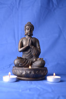 Meditating Buddah statue with candles , 2015