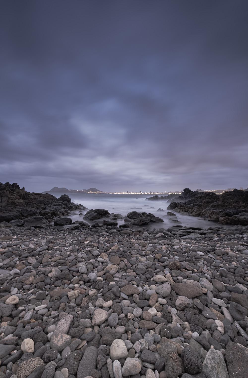 Fotografía larga exposición con filtro ND de 10 pasos. El bajo de Agustín diablo. Playa de callaos con roca volcánica. Las Palmas de Gran Canaria