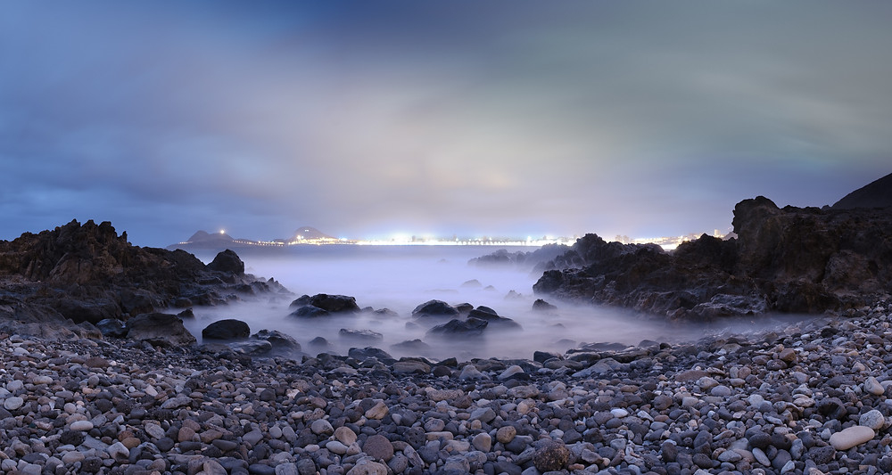 Fotografía de larga exposición en una playa de callaos con roca vocánica en El bajo de Agustín diablo. En la carretera del norte de Gran Canaria