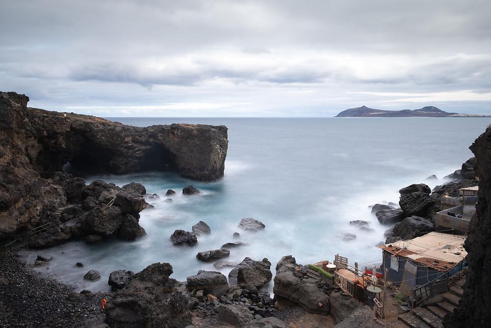 Fotografía de larga exposición de la playa de Punta de Arucas con La Isleta, al fondo y humildes casas en el primero plano
