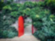 Open, red, half-round door in a brick wa