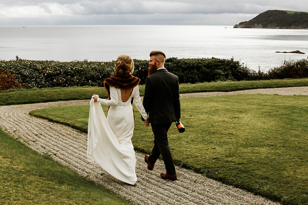 Bride and groom walking to the beach through the garden after their wedding at Porthpean House