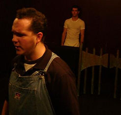 A man in coveralls has his back turned to another man on stage.