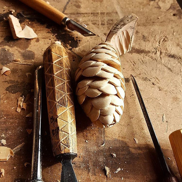 Conifer cone carved but not fully undercut.