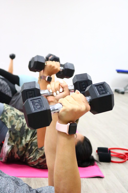 K-Fit women raise their dumbbells