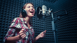 young woman in a sound studio singing into a mic