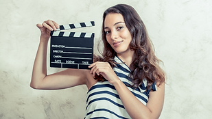 young woman with a movie slate smiling