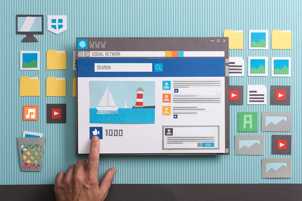 A picture of social media screen like Facebook on a computer screen with a person pressing a like button
