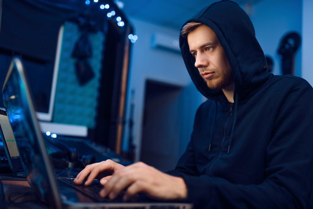 Man wearing hoodie typing on a laptop