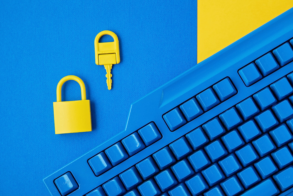 Yellow key and padlock placed above a blue keyboard