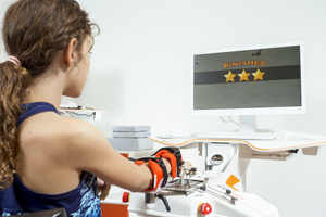 Ein Mädchien trainiert ihre Hand mit dem Handtherapie Gerät Amadeo