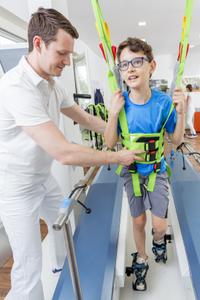 Ein Junge lernt unter Anleitung eines Physiotherapeuten zu gehen