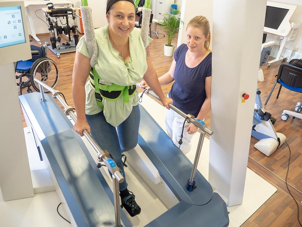 Ein Physiotherapeut begleitet einen Patienten auf den Gangtrainer. Der Gangtrainer ist ein Roboter der einem gelähmten Patienten das Lernen zu Gehen ermöglicht