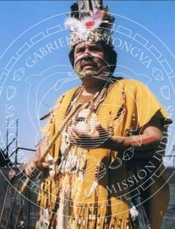 Chief Red Blood Anthony Morales poses in a traditional Gabrieleno Tongva feather headdress and regalia with a clapperstick in a color photo.