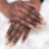 Woman with folded hands showing acrylic, gel, UV nails.