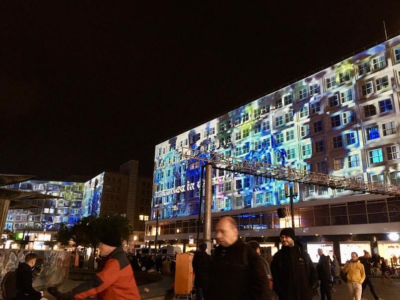 アレクサンダー広場にて、建物に投影されたベルリンの壁崩壊時の歓喜する人々の映像。