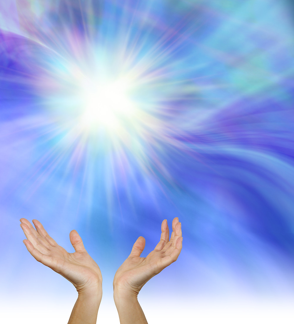 Image of hands uplifted to a blue and purple sky and white light
