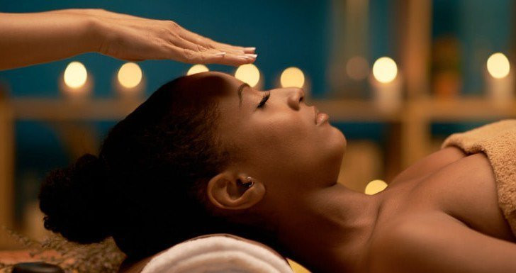 Image of an African American woman receiving reiki energy, with reiki master's hands hovering over her forehead