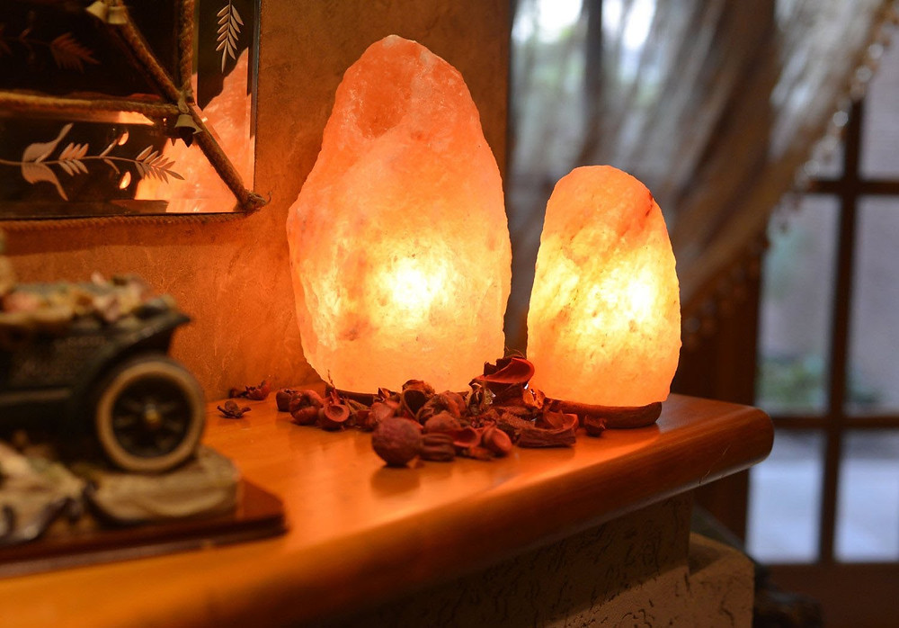 Image of 2 himalayan salt lamps of different sizes on a dresser lighting a dark room