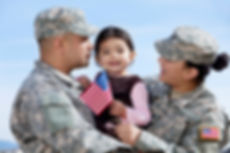 Image of military parents in fatigues, holding their young child