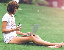 woman-holding-card-with-macbook-air-on-l
