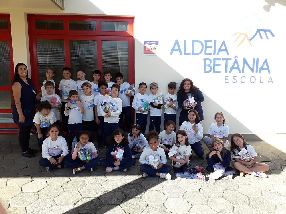 Alunos fazendo suas atividades em frente ao hall da Escola Aldeia Betânia