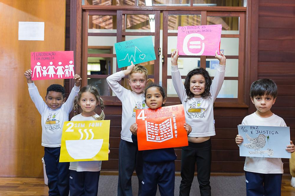 Crianças com cartazes do ODS