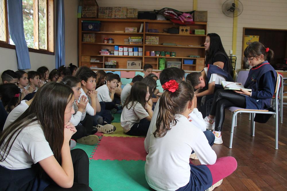 Crianças tendo uma reflexão com a Palavra de Deus orientadas pela professora