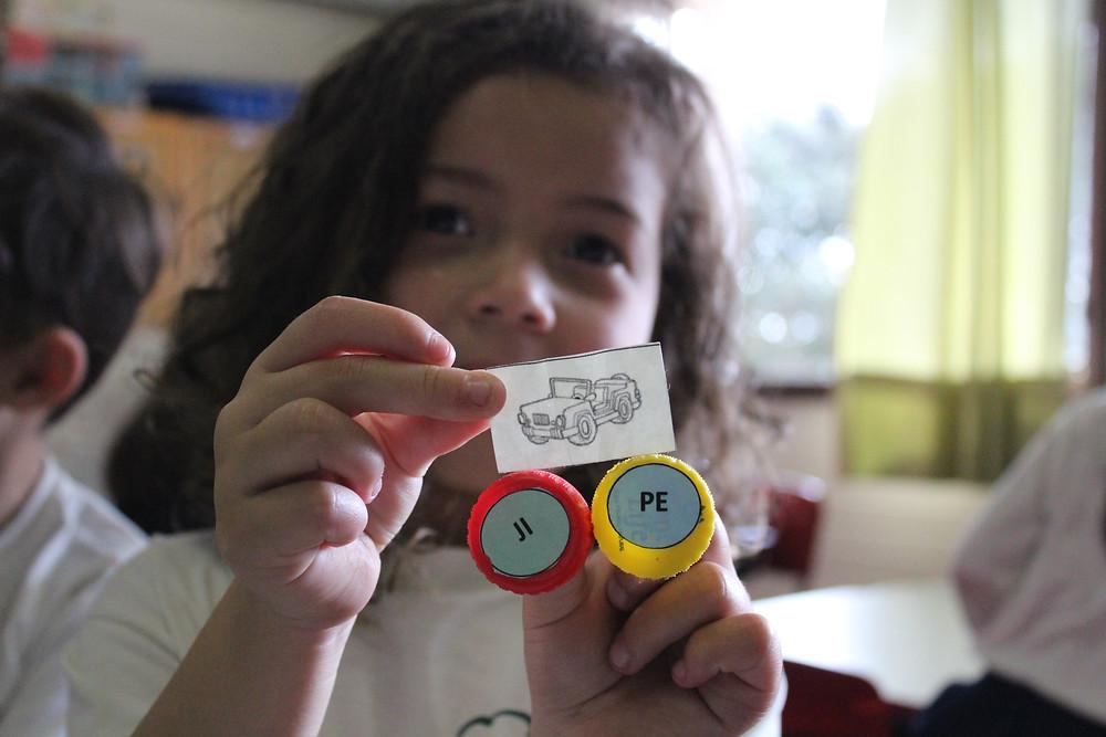 Professoras usam tampinhas de garrafa e imagens para ajudar na alfabetização.