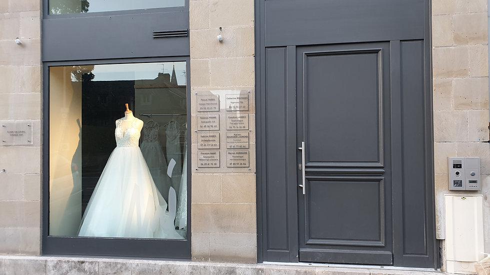 bas de l'immeuble du cabinet de Brive - à côté d'une vitrine magnifique de robe de marié
