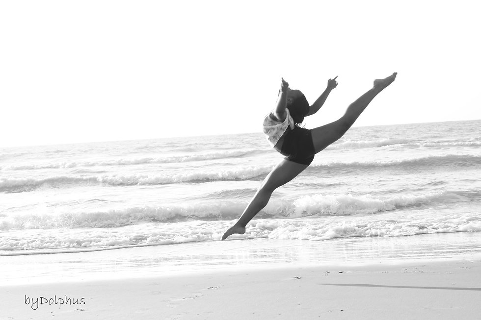 young dancer on the beach is captured doing a wide leap, with Ocean waves in the background.