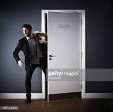 Man attempting to go through open door but is being yanked back in.