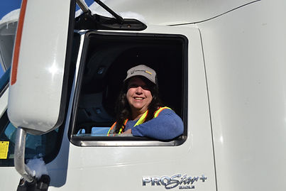 Jeannie, our Women In Trucking Scholarship recipient, sits in the truck ready to drive. Jeannie came through our program as an enthusiastic learner who found her dream job!