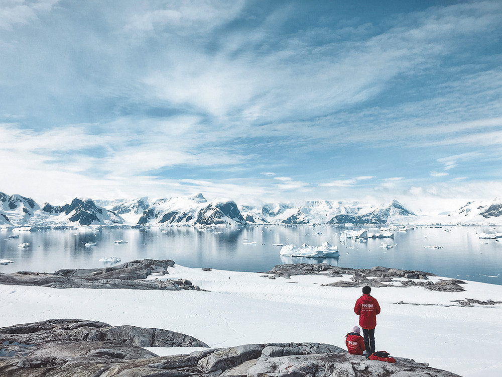 Two explorers in red jackets in the foreground with a backdrop of frozen landscape with snow, mountains and lake beneath a blue partly cloudy sky
