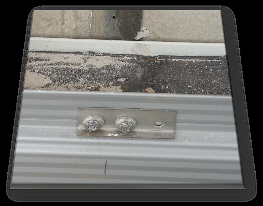 Ein mit zwei Bohrschrauben und einer Lastverteilerplatte an der Ankerschiene an einer  Stahlbetonstütze befestigtes Sandwichelement. Das Dichtband verursacht einen Abstand undefinierter Breite zwischen dem Sandwichpaneel und der Stahlbetonstütze.