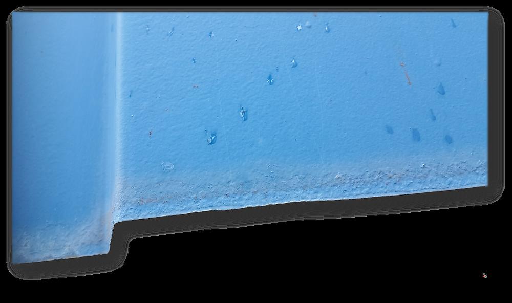 Blick auf den unteren Rand eines etwa vierzig Jahre alten Stahltrapezbleches. Trotz ausreichenden Abstandes und Luftumspülung sind deutliche Korrosionsspuren zu erkennen. Der Abtrag des Zinkmantels arbeitet sich von der Schnittkante nach oben.