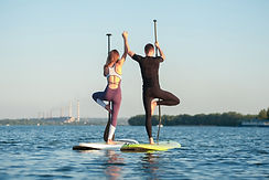 Couple engaging in a tree pose on kayaks in the water after completing couples therapy as a result of infidelity in the relationship.
