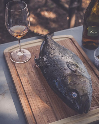 Omega Azul's Whole Round Baja Kanpachi (also known as kampachi, amberjack, or longfin yellowtail) on cutting board with white wine